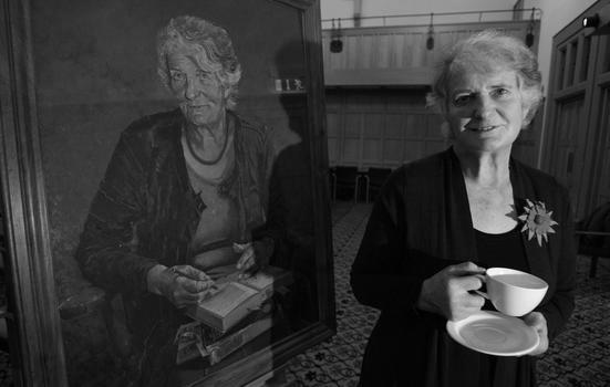 Edna Lonlgey standing next to a portrait of herself