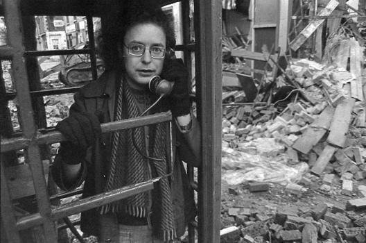 Stewart Parker standing in a phone booth in a street covered in rubble from a bombing.